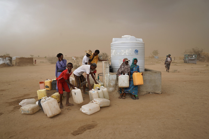 Collecting water as a sandstorm approaches in a settlement for internally displaced persons in Hajjah Governorate, Yemen. Water, carefully rationed, is available during one-hour windows, normally three times a day. © UNICEF/UN073954/Clarke for UNOCHA