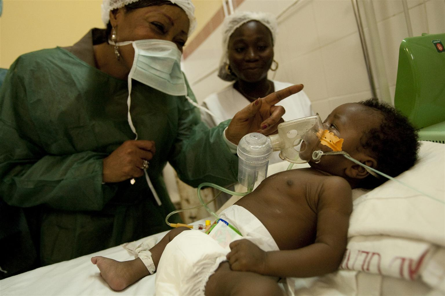Hospital Director Sidonie Kinzonzi greets a baby wearing a respiration mask at the A. Cisse Hospital in the coastal city of Pointe-Noire, the epicentre of the country's polio epidemic. The baby does not have polio.