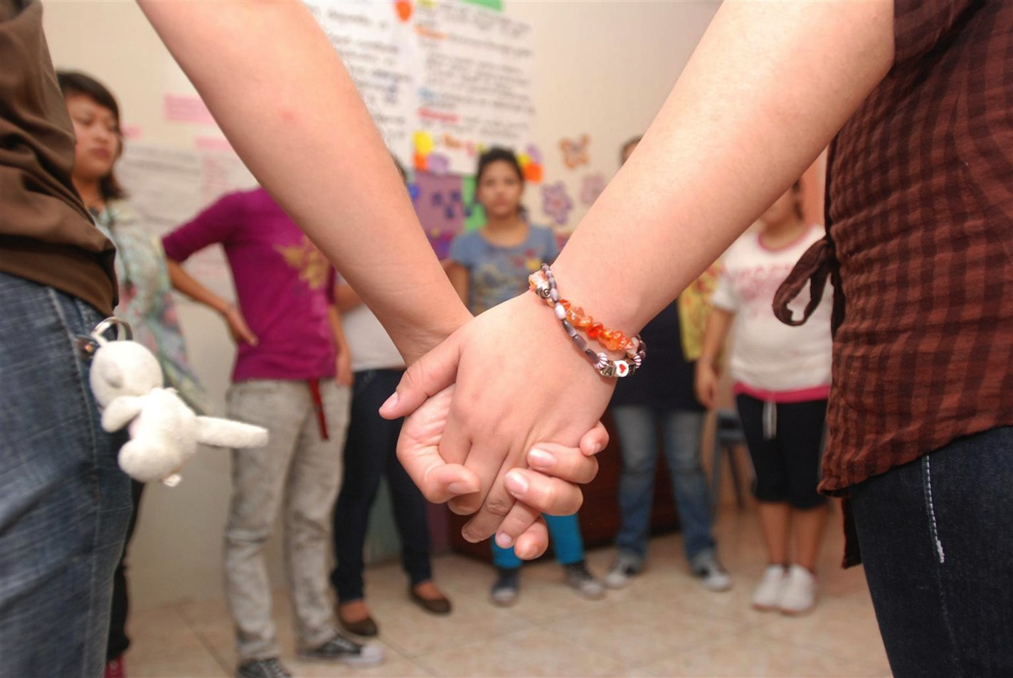 Teen girls hold hands during an activity at a UNICEF-supported children's shelter in Guatemala