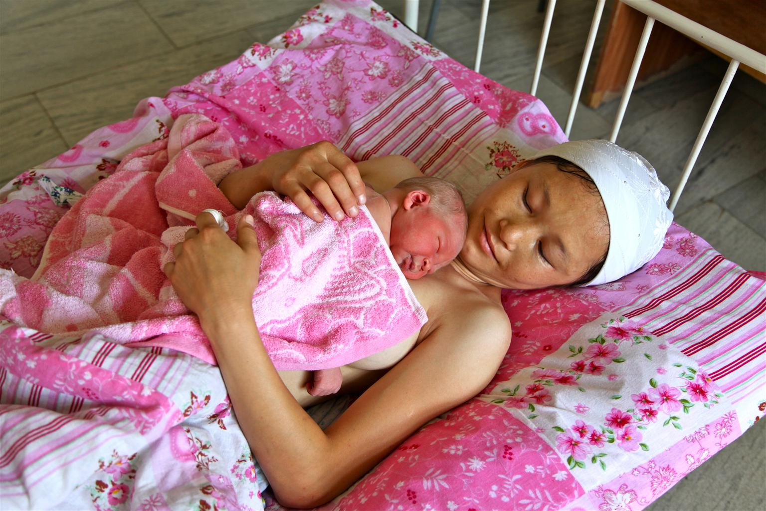 Jonsulu Shukurbaeva smiles at her newborn in the city of Khujayli's hospital in Uzbekistan.