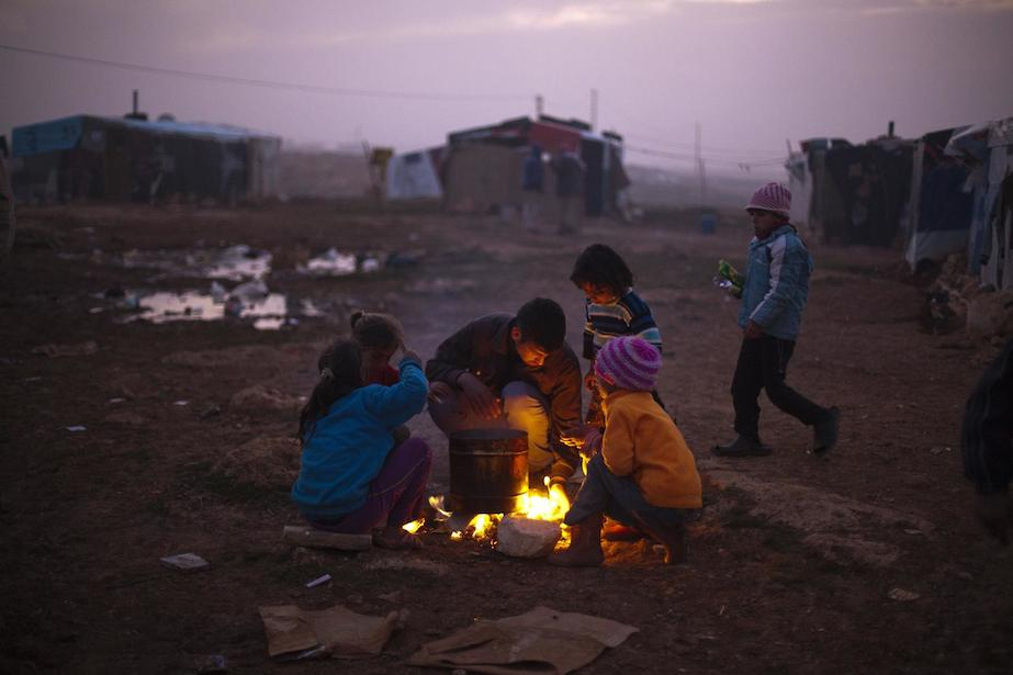 Syrian refugee children warm themselves by a fire in an encampment near Baalbek, Lebanon.