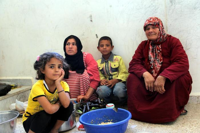 A family gathers during preparation of an evening meal during Ramadan in the rural town of Hassayia, near Homs, Syria, in 2013.