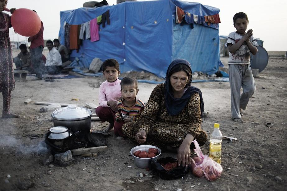 A woman and three children prepare a meal at a makeshift outdoor cooking area, in the Kawergosk camp for Syrian refugees, just west of Erbil, the capital of Kurdistan Region. By 14 November, the camp was hosting over 13,100 refugees.