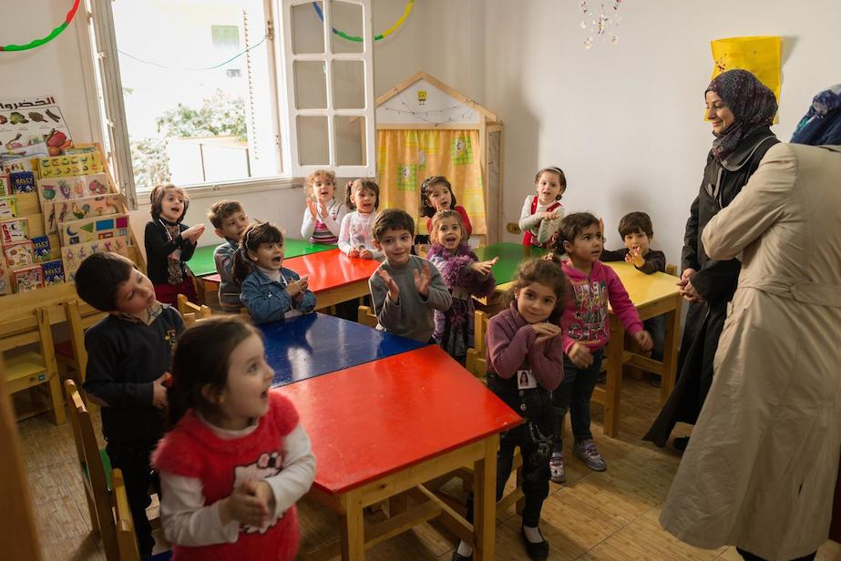 Children clap and sing during a music class in a UNICEF-supported kindergarten for Syrian refugee children, in the city of Giza.