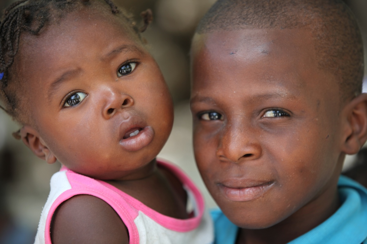 Two children at the UNICEF-supported mobile vaccination station set up outside a church by the side of the road in Haiti.
