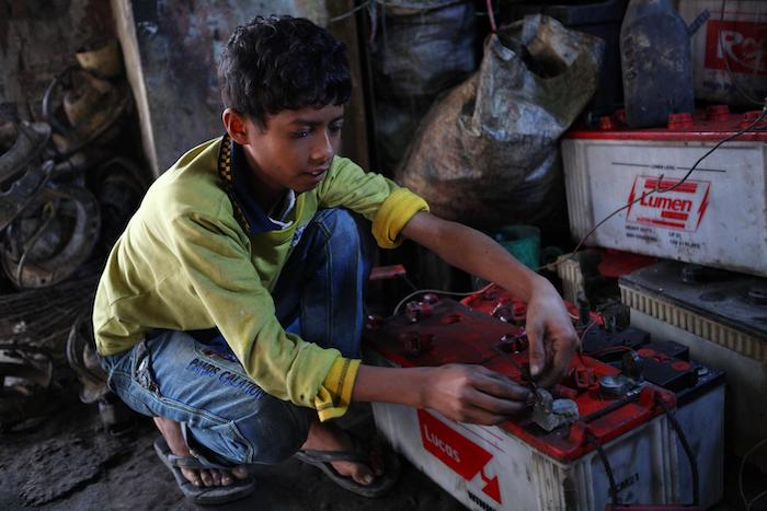 10-year-old Al Amin's job repairing batteries at a garage in Dhaka puts him at risk of lead exposure and its ill effects.
