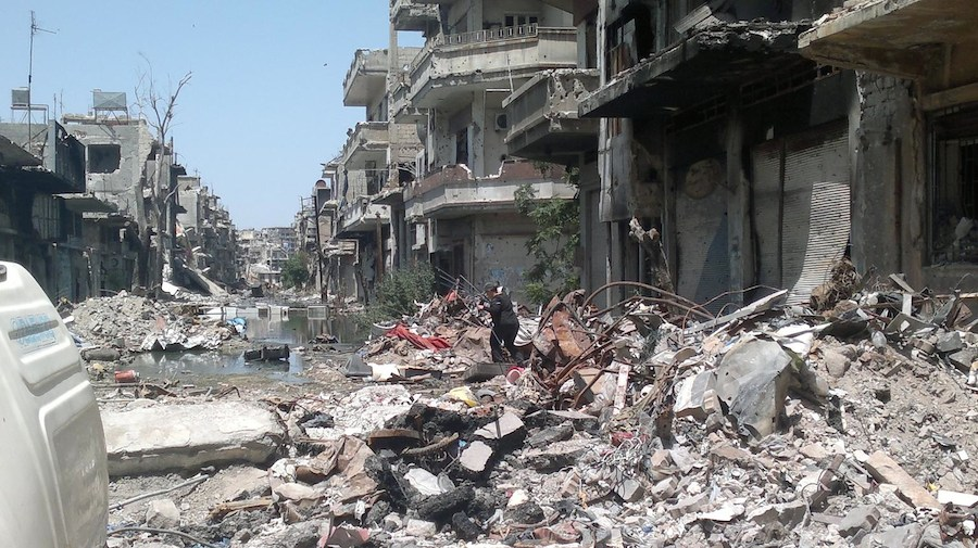 #SyriaCrisis a woman traverses a debris-covered street n the Old City area of Homs, Syria.