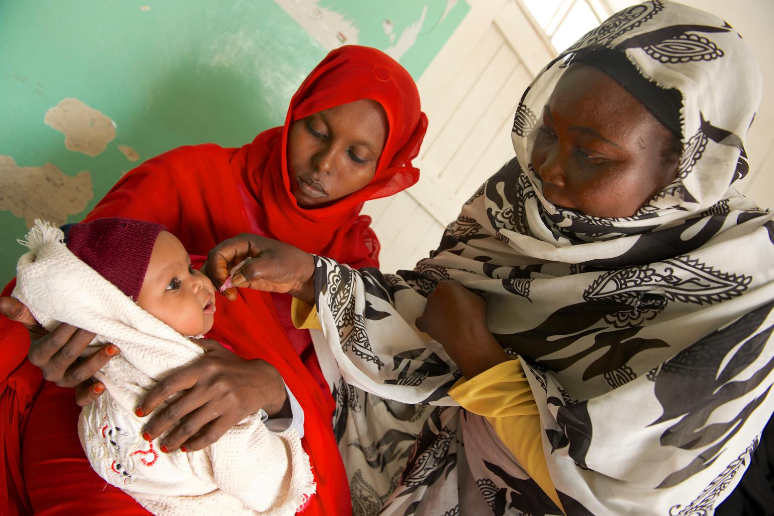 While a woman holds her child in her lap, a female health worker vaccinates the infant against polio at Qarar Ibn-e-Al Khatab Basic Health Centre in Port Sudan