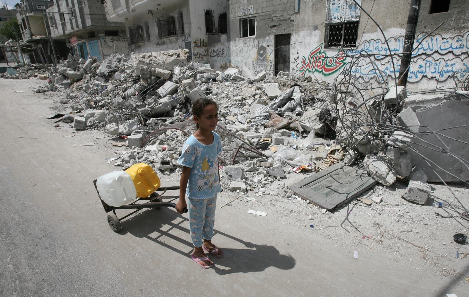 On 19 July 2014 in the State of Palestine, a girl transports jerrycans filled with water, in the town of Rafah in southern Gaza. © UNICEF/NYHQ2014-0978/El Baba