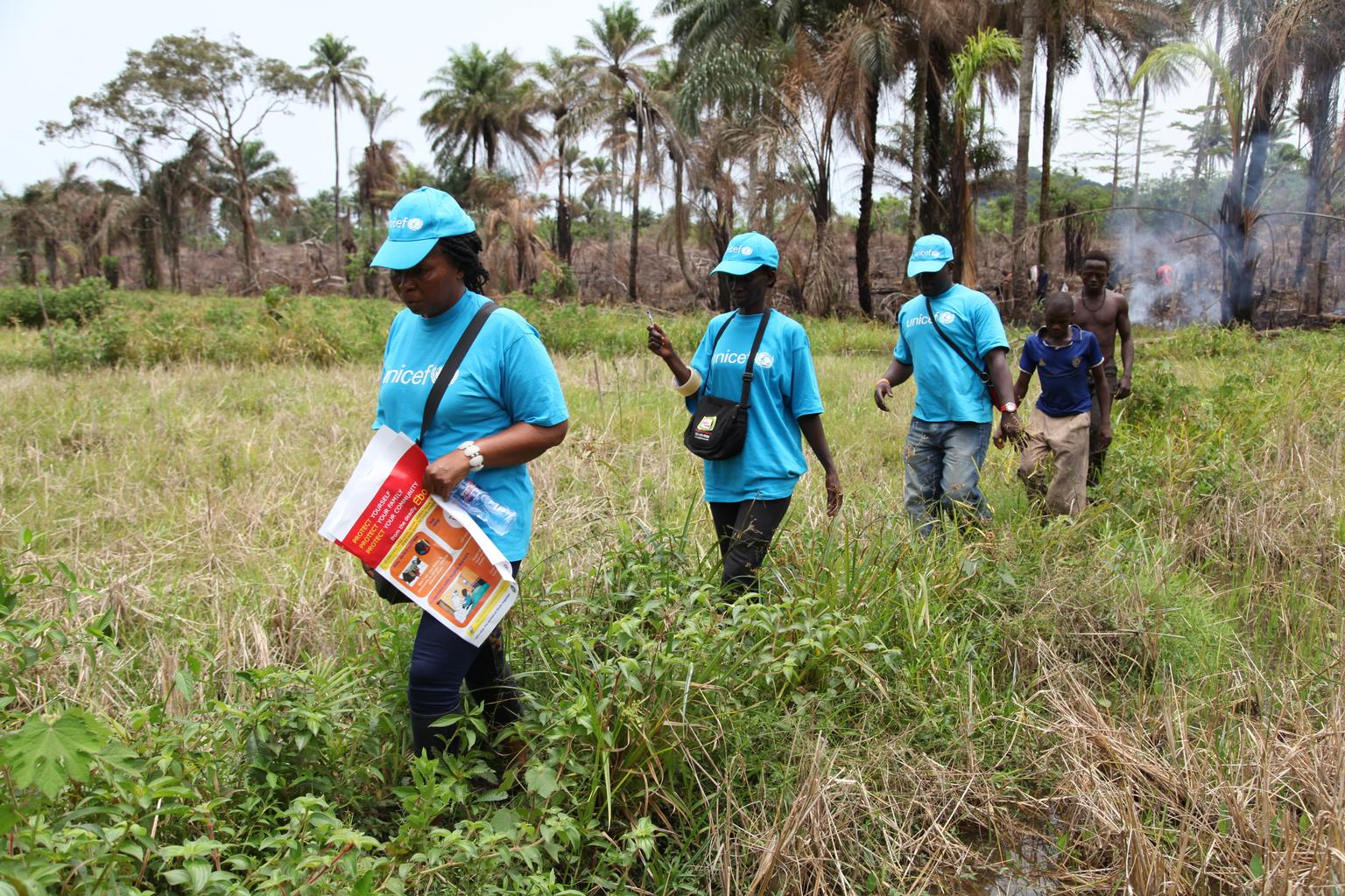 In Liberia, UNICEF workers travel by foot to reach plantation workers in a remote area, where they will share information on the symptoms of Ebola virus disease (EVD) and best practices to help prevent its spread,