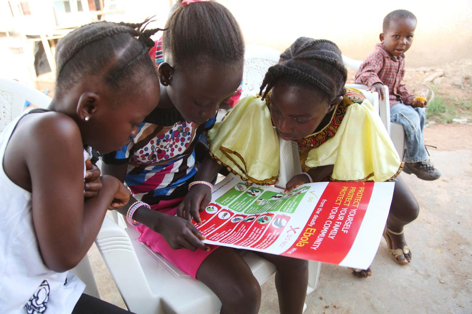 In April 2014 in Liberia, girls look at a poster, distributed by UNICEF, bearing information on and illustrations of best practices that help prevent the spread of Ebola virus disease (EVD), in the city of Voinjama, in Lofa County.