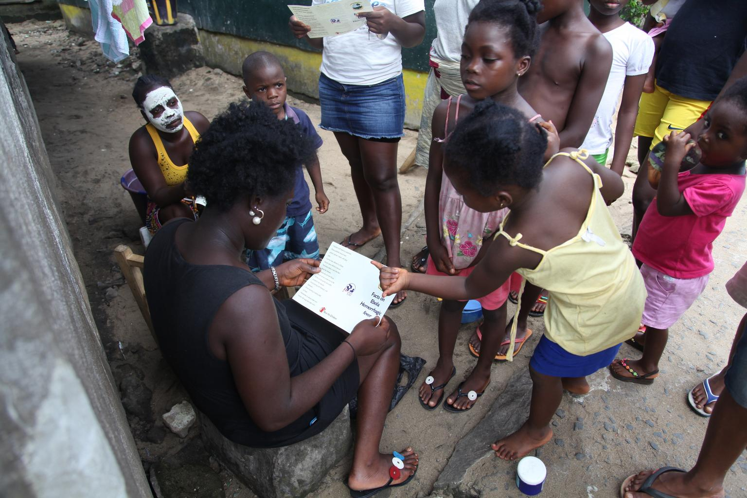 n June 2014 in Liberia, a woman reviews a brochure, distributed by UNICEF, bearing information on the symptoms of Ebola virus disease (EVD) and best practices to help prevent its spread, in New Kru Town, near Monrovia, the capital.