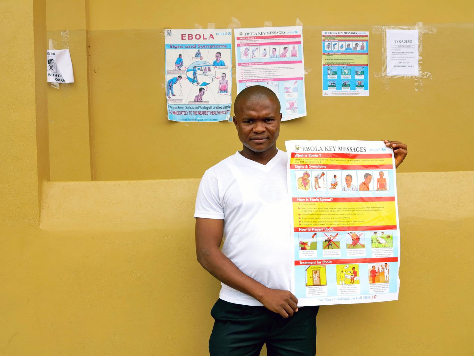 In July 2014 in Sierra Leone, Joseph Kamara, a pharmacist at Kenema Government Hospital, holds a poster bearing information on the symptoms of Ebola virus disease (EVD) and best practices to prevent its spread, in the city of Kenema, Eastern Province.