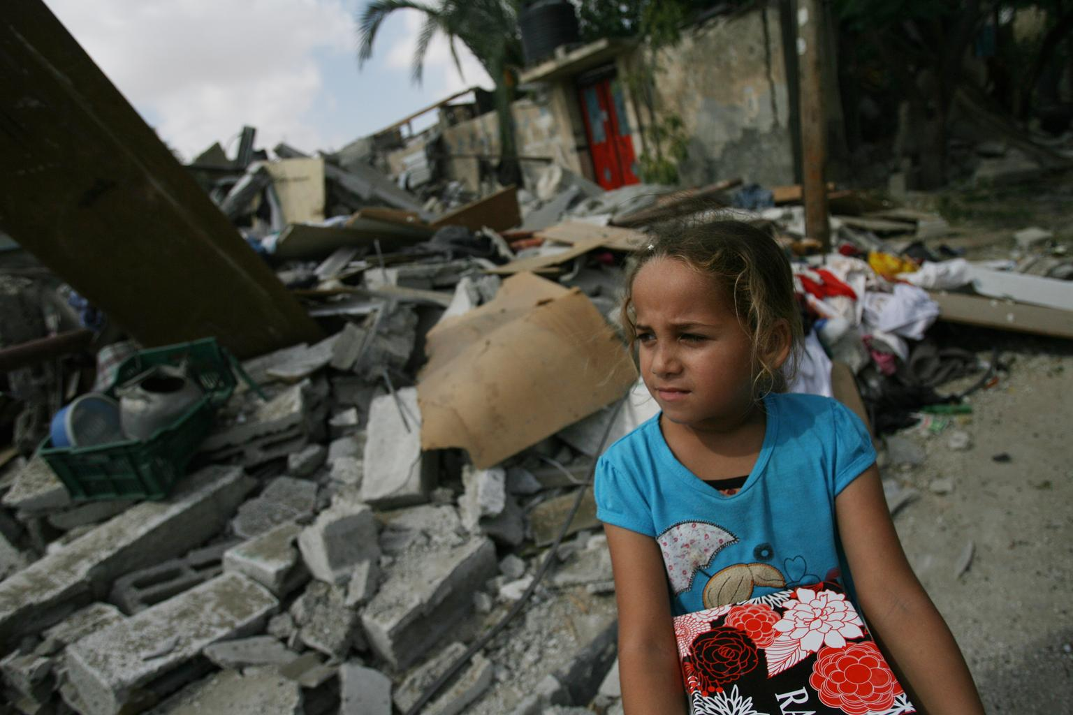 On 5 August 2014 in the State of Palestine, a girl stands amid the rubble remnants of her home, in the town of Rafah in the southern Gaza Strip. © UNICEF/NYHQ2014-1124/El Baba