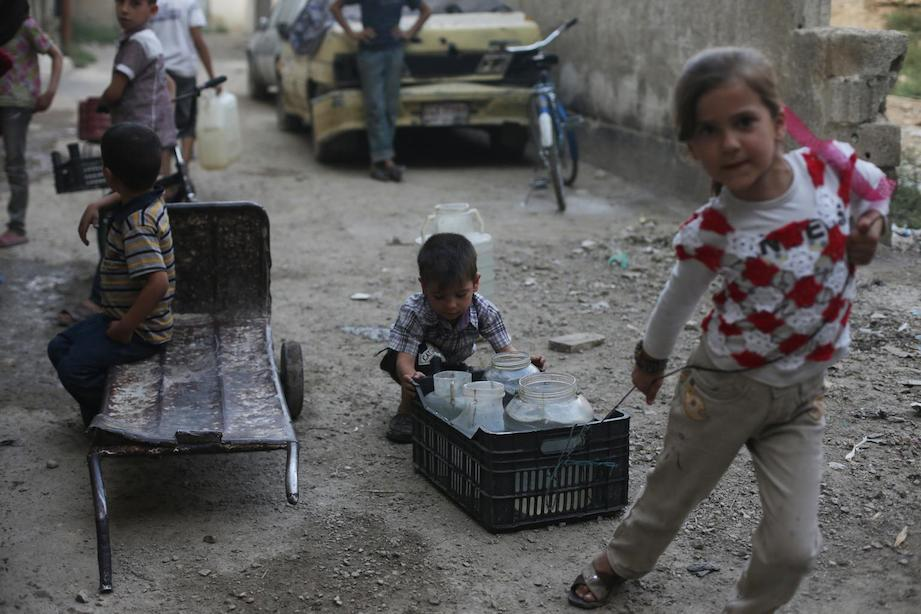 A young boy and girl push and drag a crate filled with containers of water home, in the town of Douma in the East Ghouta area of Rural Damascus, Syria.