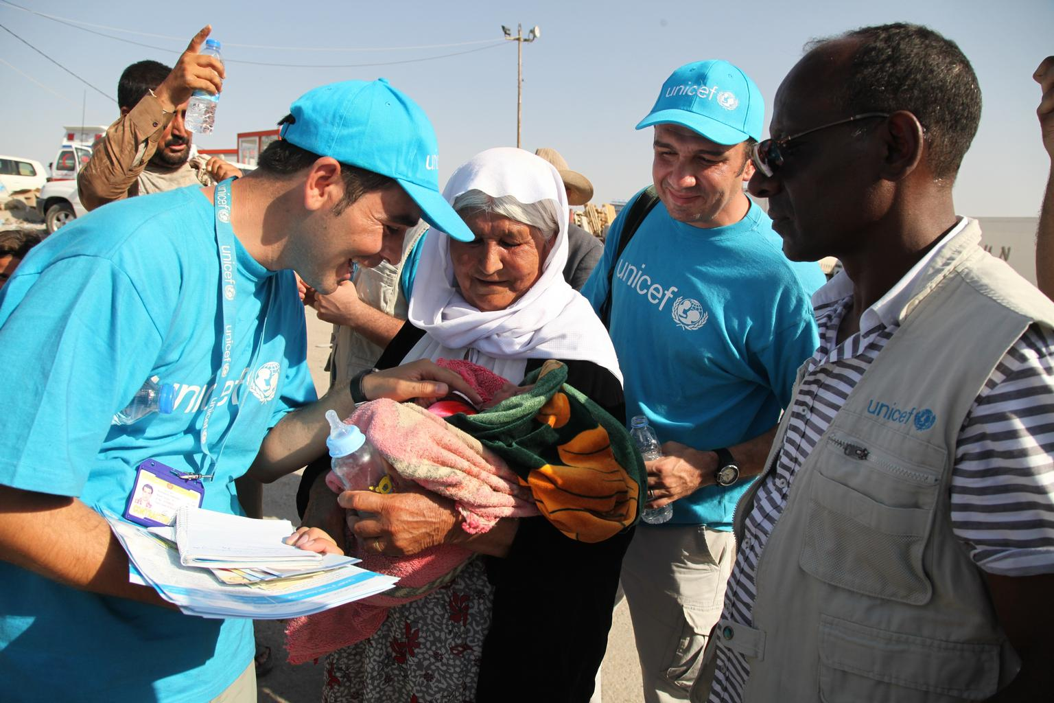 UNICEF workers interact with a 13-day-old Yazidi infant, held by an elderly woman, in the town of Peshkhabour in Dohuk Governorate.