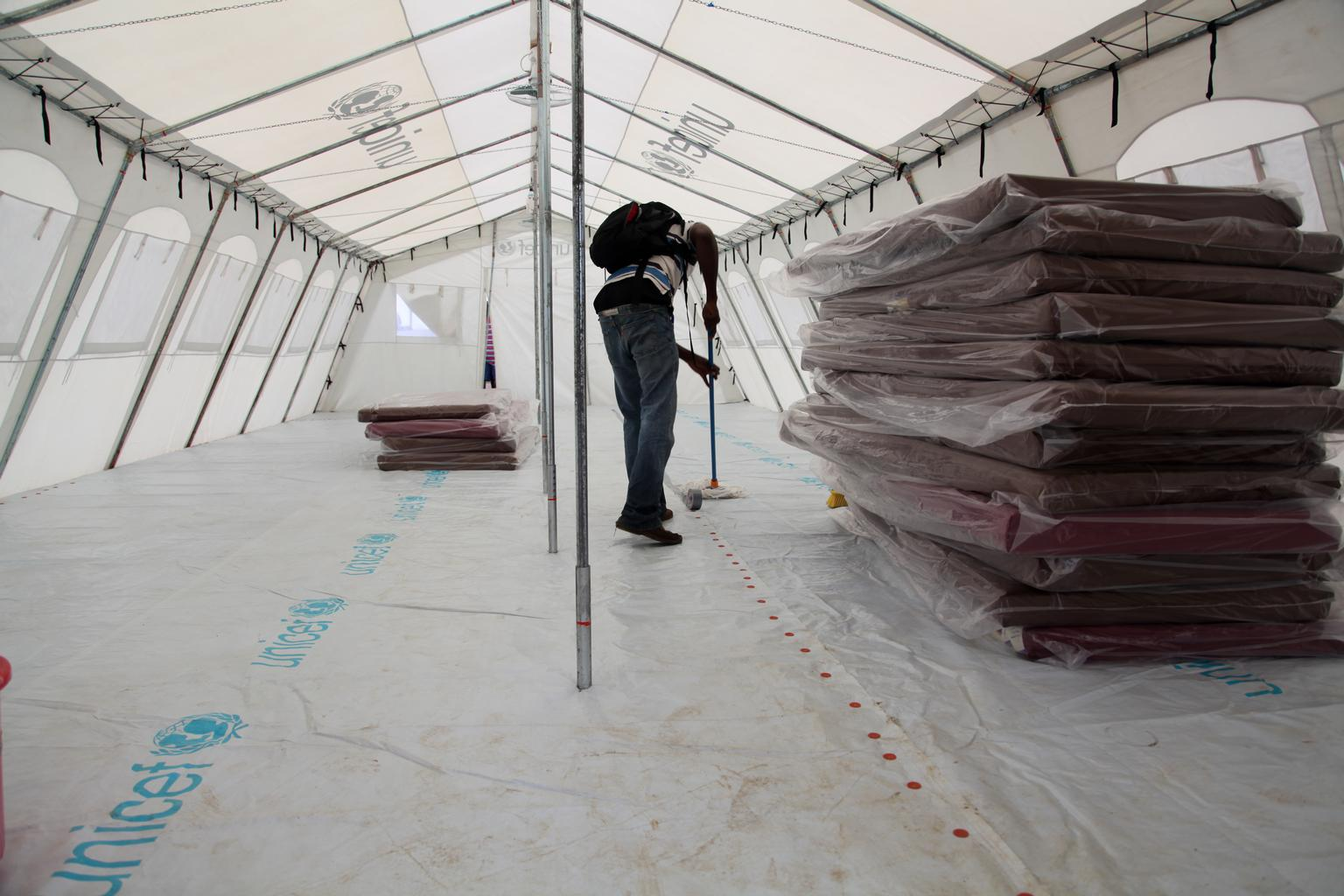 A worker cleans a newly built UNICEF tent at an expanded Ebola treatment center on the outskirts of Monrovia, Liberia. © UNICEF/NYHQ2014-1257/Jallanzo .