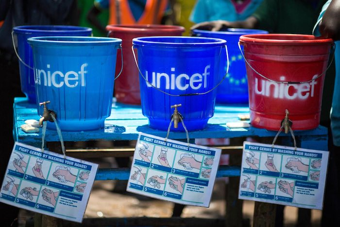 plastic buckets with taps sit on a table in Kule camp, where refugees from South Sudan have fled, 42 kilometres from Gambella town. An illustrated flyer hangs around each tap, demonstrating proper handwashing techniques that help prevent the spread of ger