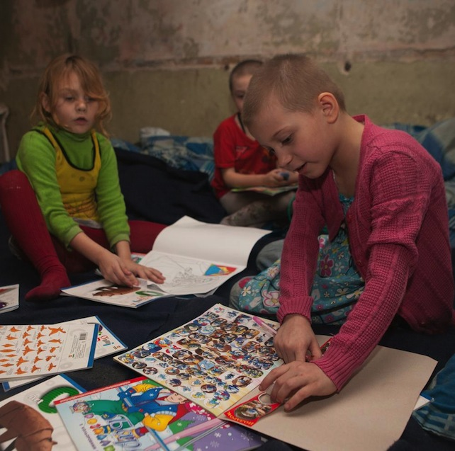 On 20 February, children play with materials from a UNICEF Ukraine education kit, in a bomb shelter, in the city of Donetsk in Donetsk Oblast.