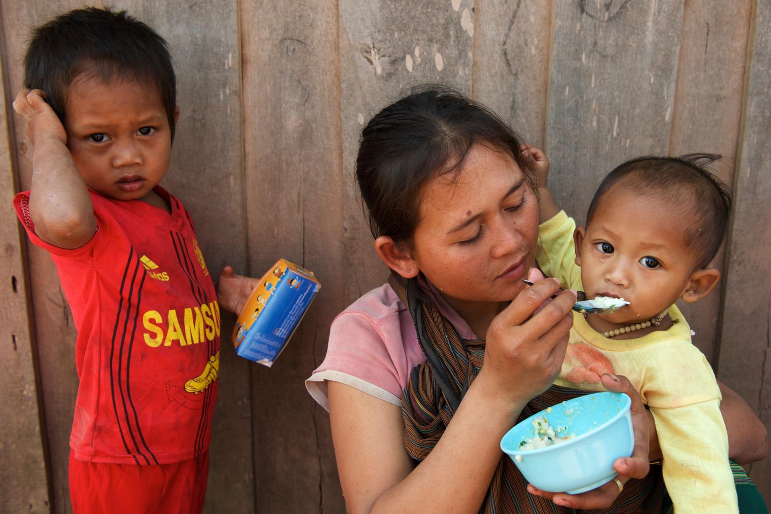 A mother from southern Lao PDR, where numbers of malnourished children are high, feeds her child cereal mixed with nutrition powder she received from UNICEF