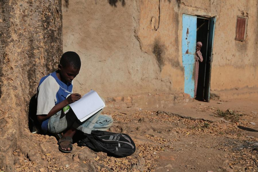 Ahmad completes his homework while seated on the ground in Moundou, Chad.