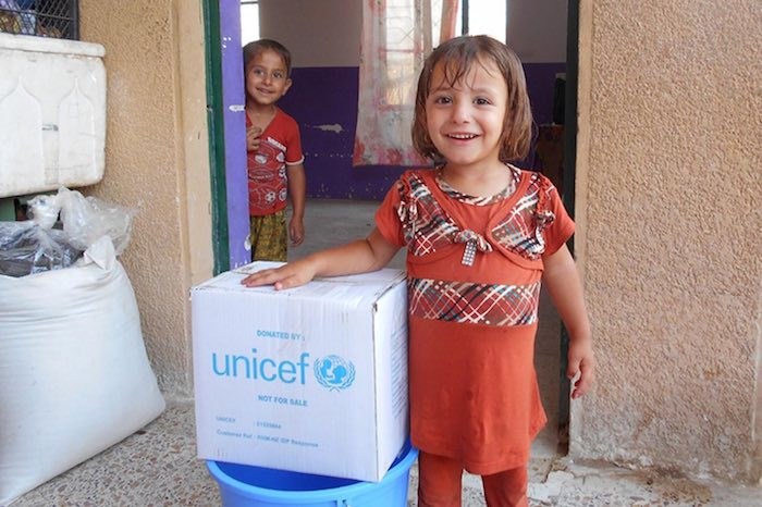 Children displaced by ongoing violence in Ramadi stand next to an RRM kit in the doorway of their informal shelter in Amriyat Al Falluja in Anbar Governorate.