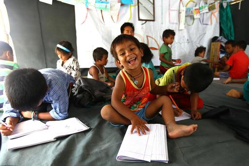 After a 7.8 magnitude earthquake hit Nepal in 2015, around 7,000 people were displaced from their homes. Here, a young child smiles as he works on lessons at the temporary learning center UNICEF set up to help kids keep up with their studies.
