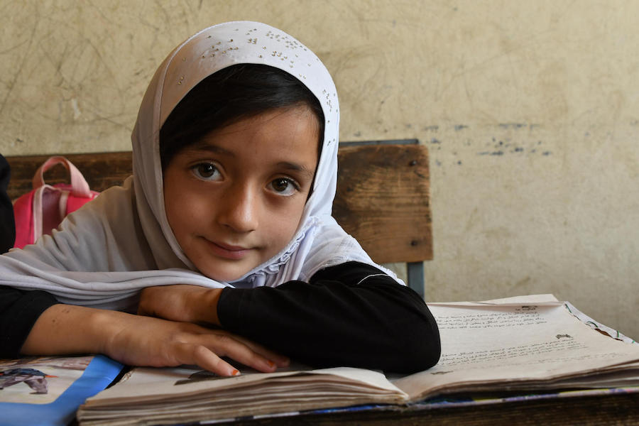 In August 2019, a girl looks up from her studies at the Turgani High School in the city of Faizabad, Badakhshan province, in northeastern Afghanistan.