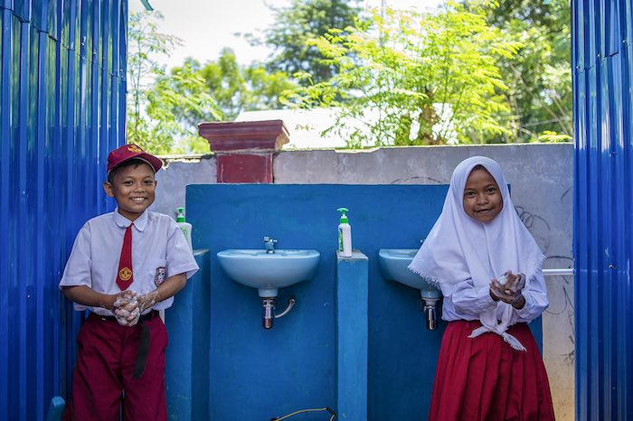 Biyan Saputra, 12 (left) and Sisil Agustin, 12 wash their hands at SDN 9 Sindue in Donggala, Central Sulawesi, Indonesia.   Sindue SDN 9 school building was damaged by the earthquake that took place in Palu on 28 September, 2018. As part of the emergency