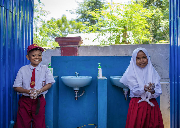 On September 9, 2019, 12-year-olds Biyan (left) and Sisal wash their hands at a sink set up by UNICEF at their school in Donggala, Central Sulawesi, Indonesia.