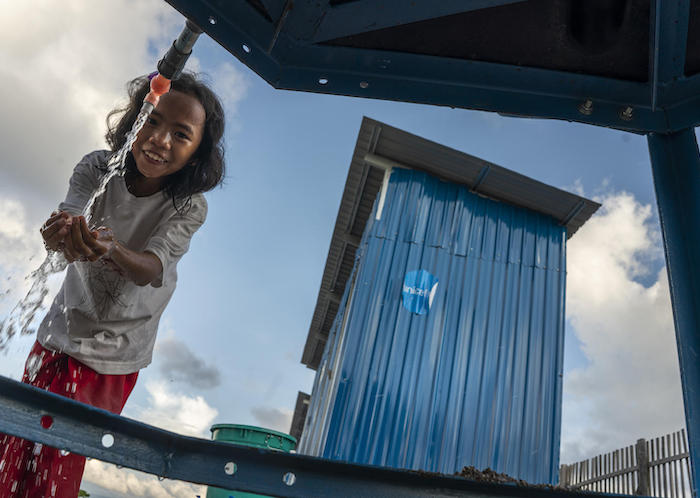 In Donggala, Central Sulawesi, Indonesia, a girl washes her hands near toilets built by UNICEF in temporary shelters for survivors of the September 2018 earthquake and tsunami.