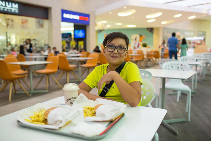 On August 27, 2019 in Almaty, Kazakhstan, 10-year-old Yerzhan poses with his fast food lunch: two hamburgers with french fries and a milkshake.