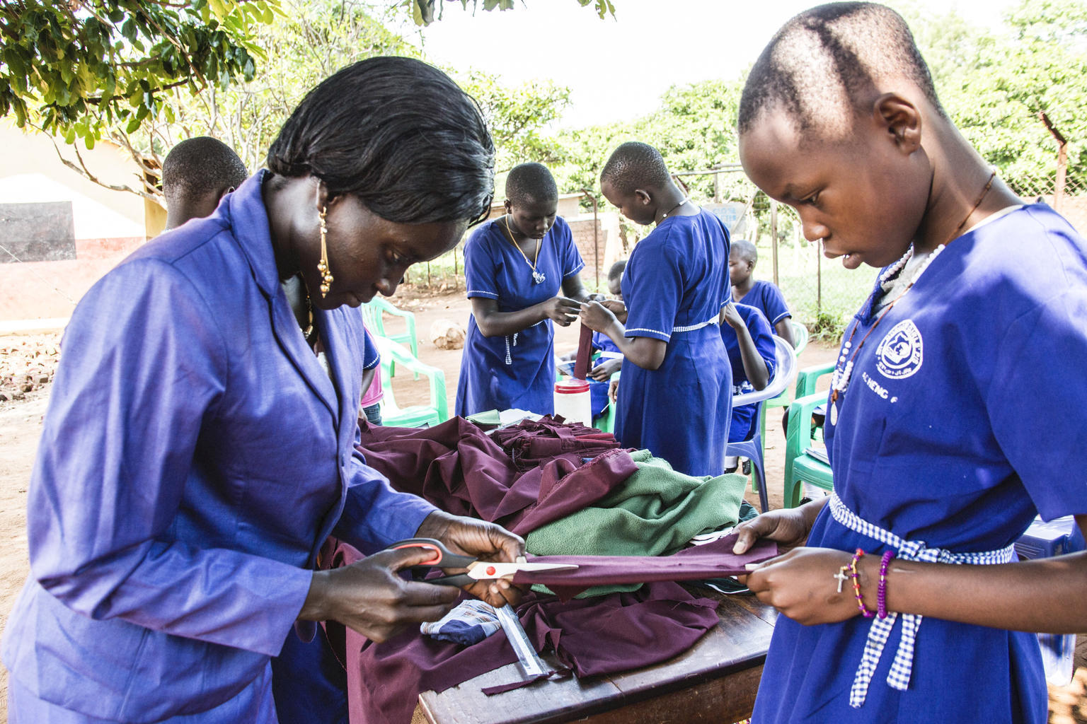 Rose Akol (left) the Senior Woman Teacher of Morulem Girls Primary Schools, demonstrates to members of the school club of Morulem Girls Primary School in Abim District in Uganda, how to make reusable pads. This activity was one of many supported by UNICEF