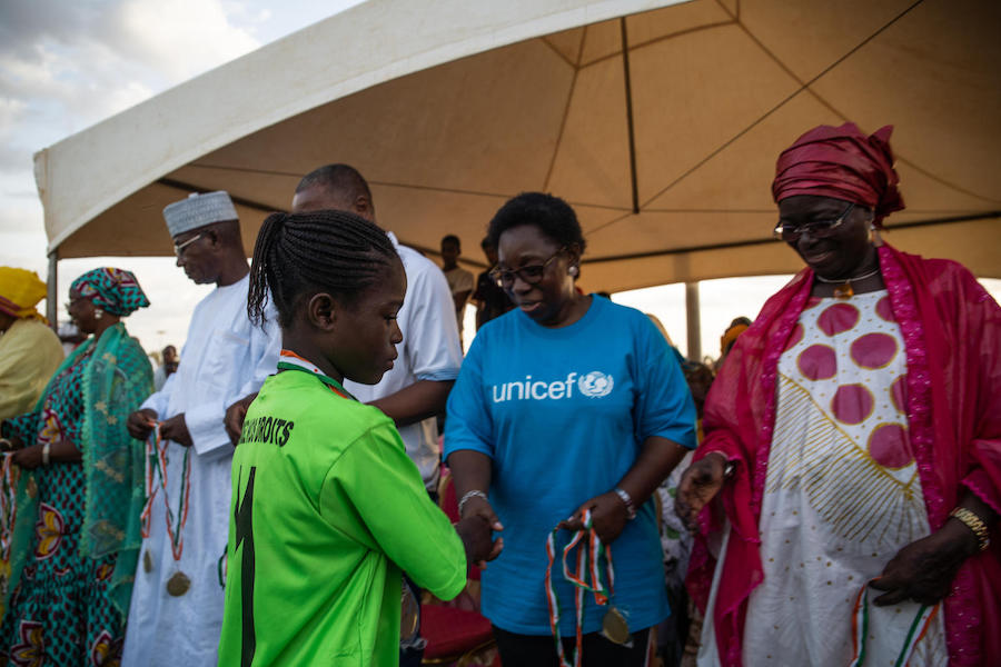Félicité Tchibindat, UNICEF's Representative in Niger, congratulates Pascaline, a student at UNICEF-supported Academie Atcha in Niamey, a program that helps out-of-school children get an education by combining academics and athletics.