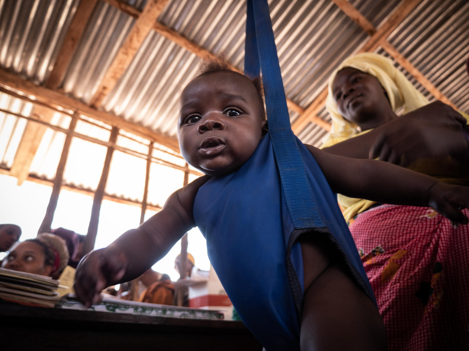 On 27 September, 2019, a boy is weighed, as his mother looks on, during a checkup at a community outreach medical clinic in a village near Mecufi, northern Mozambique.