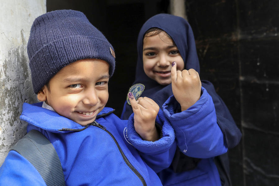 Five-year-olds Abdullah (left) and Mariyam show the ink marks confirming they have received the polio vaccine in the Ponch house area of Lahore Punjab Province, Pakistan in January 2019.