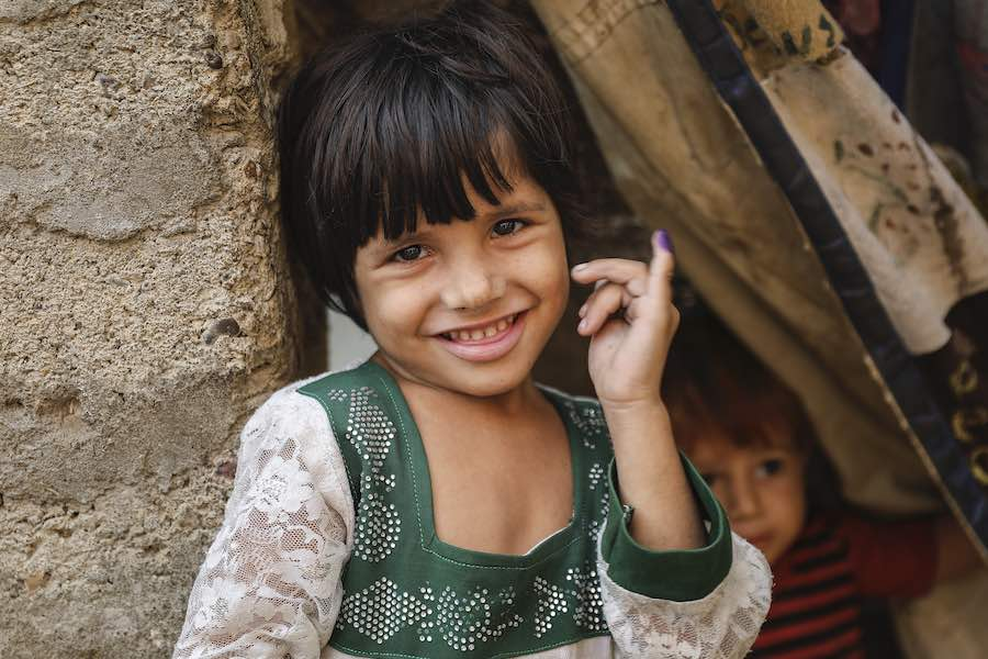 Anila (4) shows ink mark on her little finger, which confirms that she has received polio vaccine during Polio – National Immunisation Day (NID) in Gadab town, Karachi Sindh Province, Pakistan.