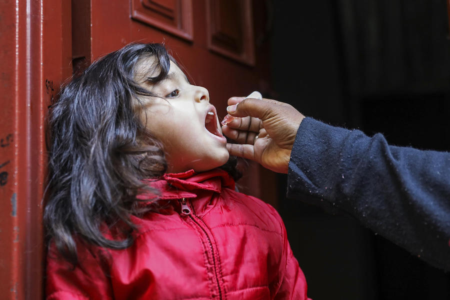 UNICEF-supported vaccinator Shaima Shahid vaccinates Aneesa, 4, against polio at her front door in the Bhatti gate area of Lahore Punjab Province, Pakistan in January 2019.