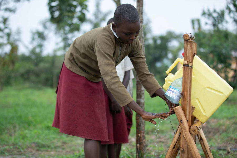 In 2019, a student at the Damasiko Primary School in western Uganda's Kamwenge district uses a tippy tap to wash her hands with soap, part of a UNICEF-led water, sanitation and hygiene improvement program.