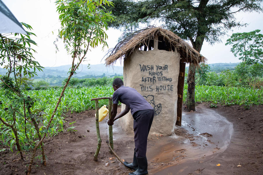 Nsemirirwe Aarons washes his hands outside his family's latrine in western Uganda's Kamwenge district. They added the tippy tap after attending a UNICEF education session in 2019.