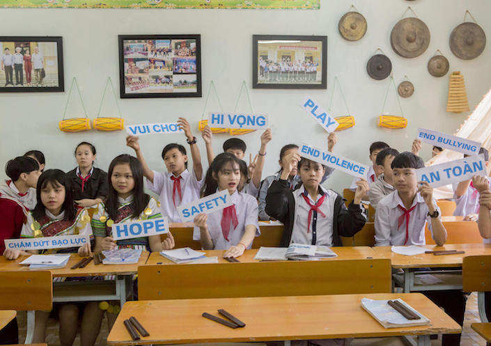 Students at a UNICEF-supported high school in Vietnam hold up signs showing their concerns for the future.