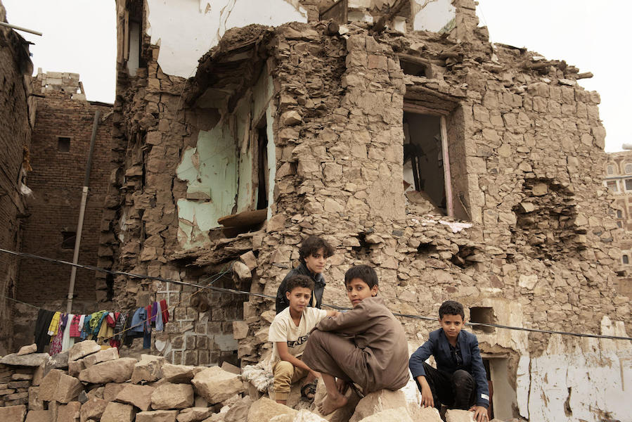 Children sit in front of a house damaged by an air strike inside the old city of Sana'a, Yemen on July 20, 2019.