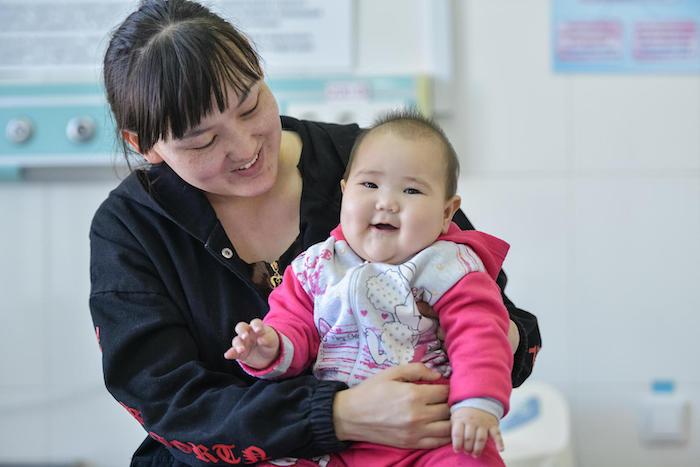 On March 13, 2019, 7-month-old Aisezim smiles on her mother's lap after being treated for pneumonia in the emergency room of a UNICEF-supported clinic in Turkestan, Kazakhstan.