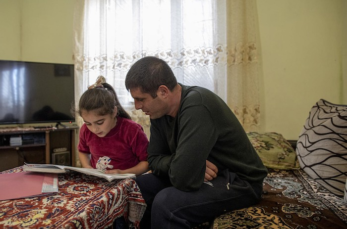 Hripsime Melqonyan, 9, (left) does homework with her father Vladimir Melqonyan, 38, at the family's home in Gyumri, Armenia,