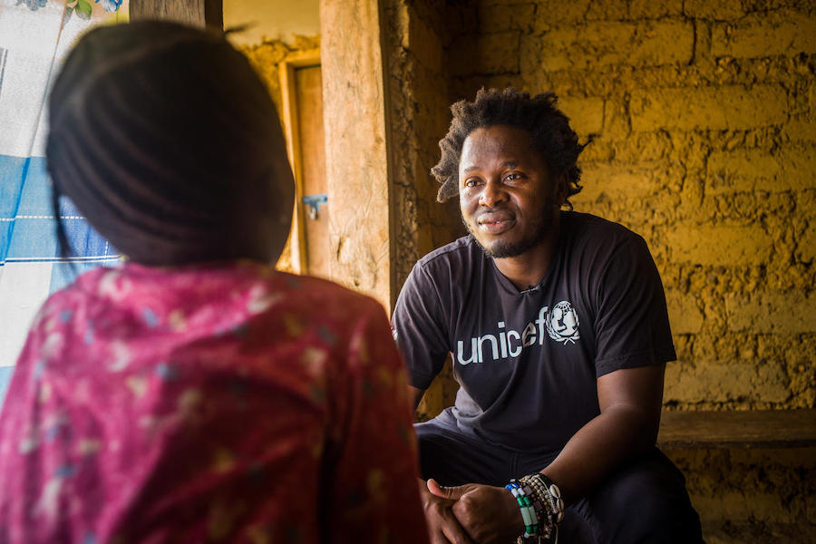 Former child soldier and UNICEF Goodwill Ambassador Ishmael Beah talks with 8-year-old Adama*, who was sexually abused by a teacher at her school in Sierra Leone's Tonkolili district. (*Name changed for her protection)