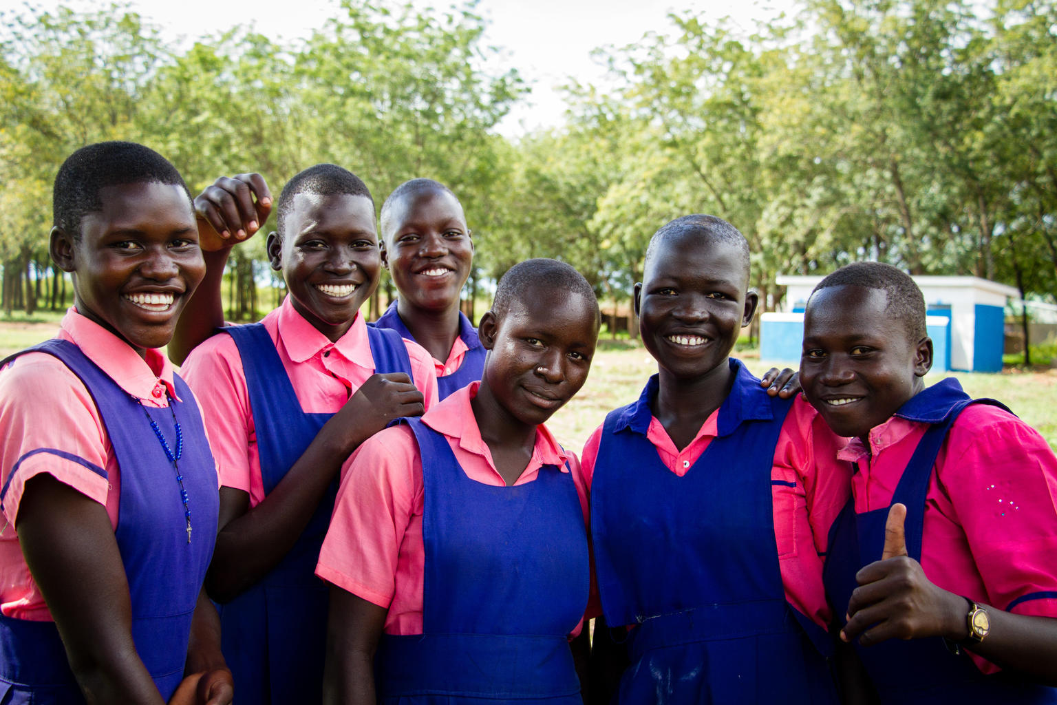 Female students pose in front of the new UNICEF funded bathrooms at Umwia Primary School in Adjumani District, Northern Uganda. Girls can now stay in school comfortably during menstruation. © UNICEF/UNI232820/Bridger