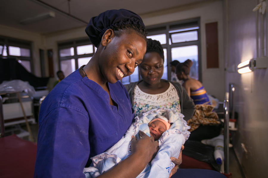 In Uganda, UNICEF-supported midwife Uwingabire Mary joyfully holds the firstborn baby of Kabugho Moureen, 23.