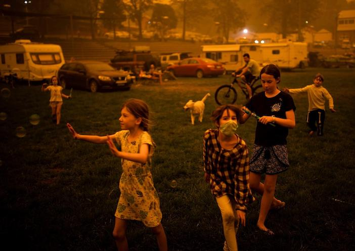 Children play at the showgrounds in the southern New South Wales town of Bega where they are camping after being evacuated from nearby sites affected by bushfires on December 31, 2019.