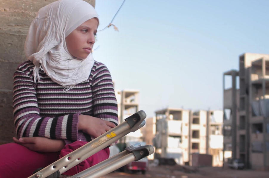 In Aleppo, Syria in 2016, 12-year-old Saja watches friends playing football. She lost her leg in a bomb blast at age 11.