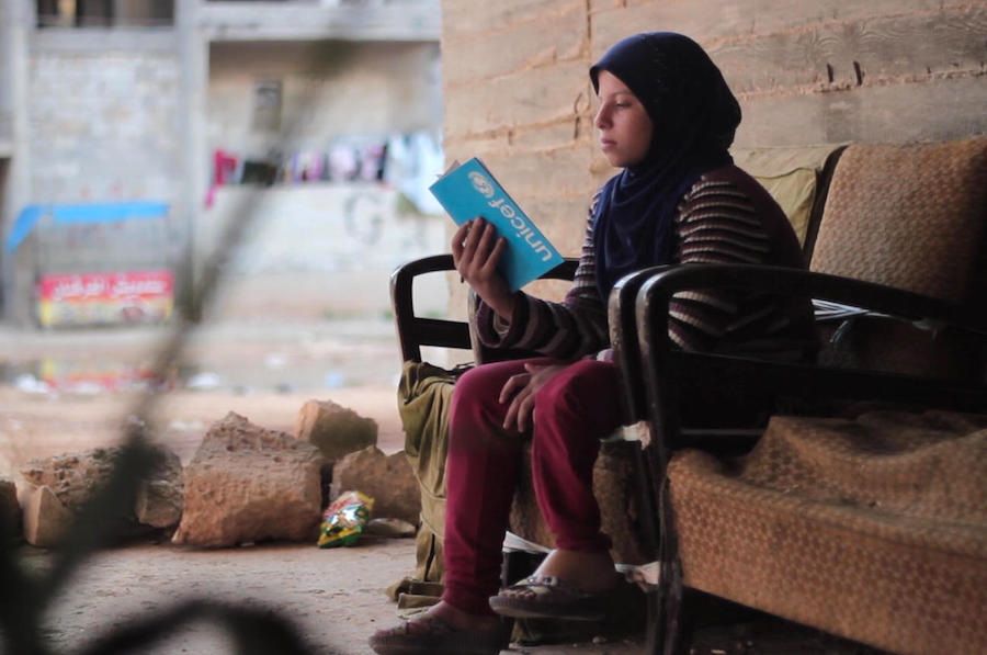 In Aleppo, Syria in 2016, 12-year-old Saja reads from a UNICEF notebook. She lost her leg in a bombing attack on her neighborhood, but is back in school and hoping to compete in the Special Olympics one day.